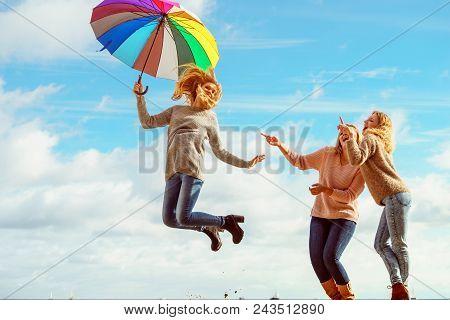 Three Women Full Of Joy Jumping Around With Colorful Umbrella. Female Friends Having Fun Outdoor.