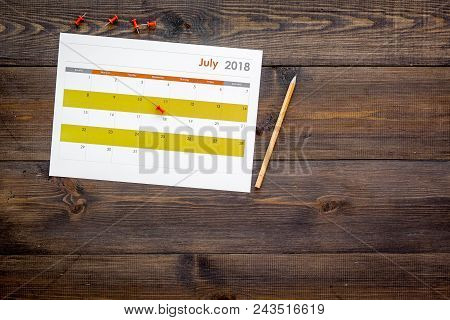 Planning. Point the date in calendar by pushpin. Set the goal. Choose date. Calendar on dark wooden background top view. poster