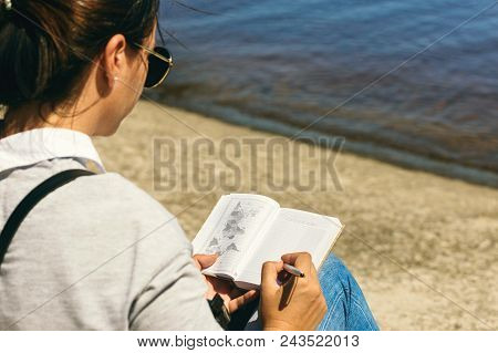Young Woman Writing In Notebook List Of Countries To See On The Beach On Sunny Day. List Of Travel C