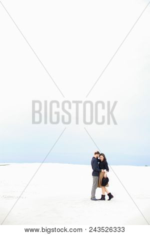 Young Couple Standing In White Winter Monophonic Background And Hugging. Woman Wearing Skirt. Concep