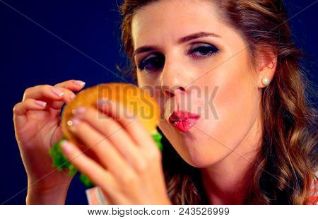 Woman eating sandwich. Girl with pleasure eats burger after diet. She opened her mouth, holding a hamburger on his outstretched hands and closed her eyes. She eats slowly, with feeling.