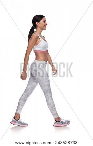 side view of smiling fitness woman walking to side for a warm up, on white background. She is wearing a pair of white leggings and a white top