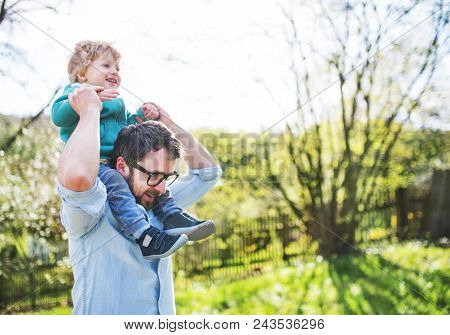A Father With His Toddler Son Outside In Green Sunny Spring Nature, Having Fun. Copy Space.