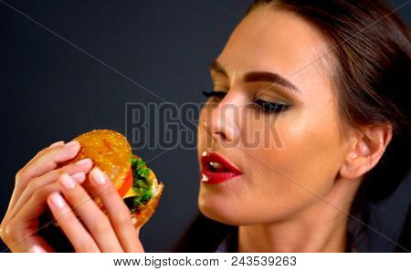 Woman eating hamburger. Girl wants to eat burger. Proper nutrition improves health. Portrait of person with good appetite have greedily dinner. As there is something that you want and do not get fat.