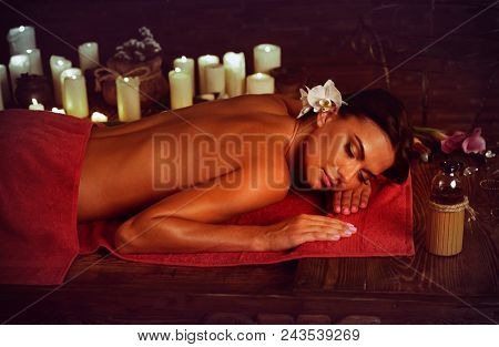 Massage of woman in spa salon. Girl on candles background in massage spa salon. Luxary interior in oriental therapy salon. Summer discounts on spa treatments. Anti-cellulite measures.