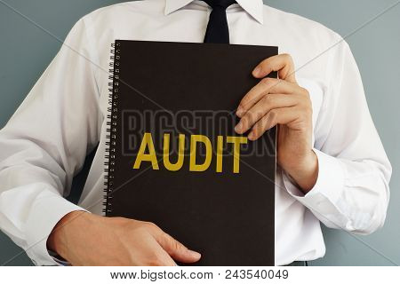 Audit Concept. The Auditor Is Holding Book.