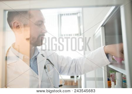 Contemporary practitioner taking something from shelf during work in his office