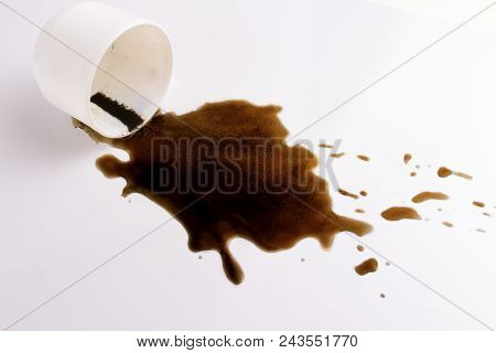 White Cup And Spilled Black Coffee On A White Background.