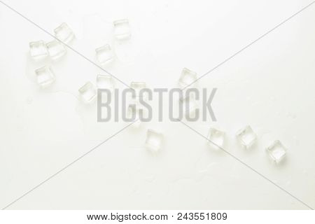 Cubes Of Ice And Spilled Water On A Light Background.