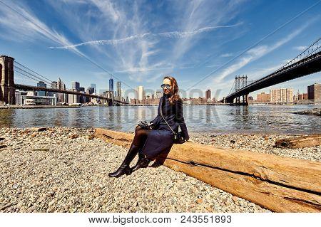 Woman sitting on shore between Brooklyn Bridge and Manhattan Bridge in New York City
