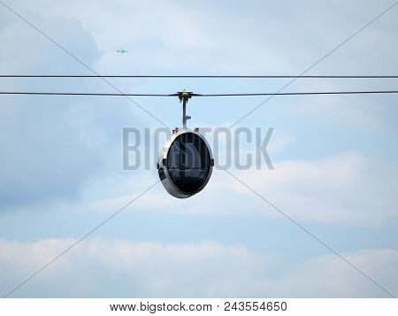 Cable Car Cabin Against The Cloudy Blue Sky. Cabin Of Ski Lift
