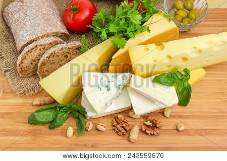 Top View Of Pieces Of Different Soft, Semi-soft, Medium-hard And Hard Cheese Among Of Brown Bread, N