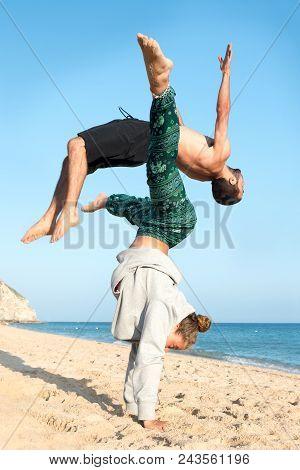 Teen Couple Doing Gimnastics In The Beach