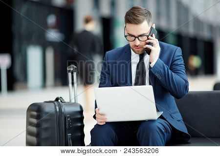 Busy agent in suit sitting in lounge of airport, making working calls and looking through online data in laptop