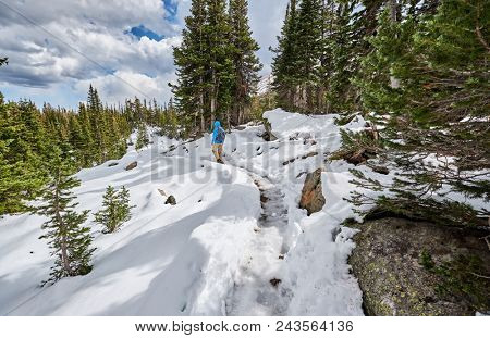 Tourist with backpack hiking on snowy trail in Rocky Mountain National Park, Colorado, USA.