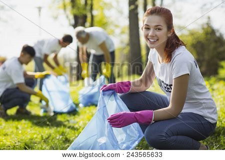 Volunteering In Park. Joyful Female Volunteer Grinning While Gathering Rubbish