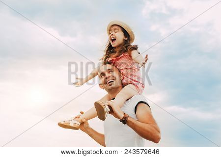 Little Girl Sitting On Father's Shoulders