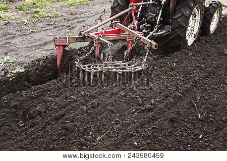 Farmer Preparing Land For Sowing. Tractor Working On The Farm, A Modern Agricultural Transport, Work