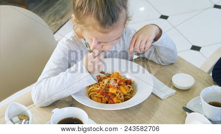 Little Grimy Girl Eating Careless Her Pasta In Cafe. Professional