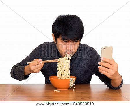 Man Eating Chinese Noodle Monstrously Whilst Looking And Using Smartphone Isolate On White Backgroun
