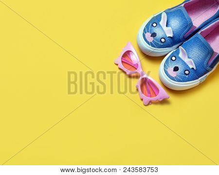 Kid's Shoes And Pink Sunglasses On Yeallow Background. Top View, Flat Lay. Place For Text. Fashion C