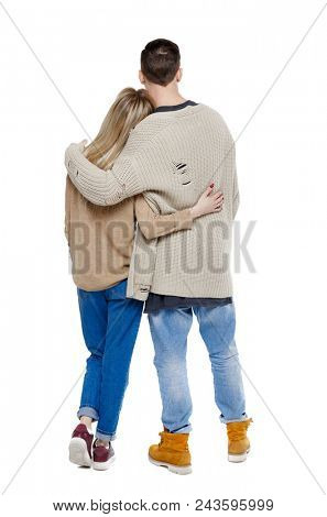 Back view of a stylish couple. beautiful friendly girl and guy together. Rear view people collection.  backside view of person.  Isolated over white. Young guy and girl hug looking at something