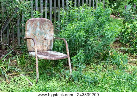 Empty Old, Weathered Chair Against A Slat Fence And Greenery, Aging Death And Grief Concept, Horizon