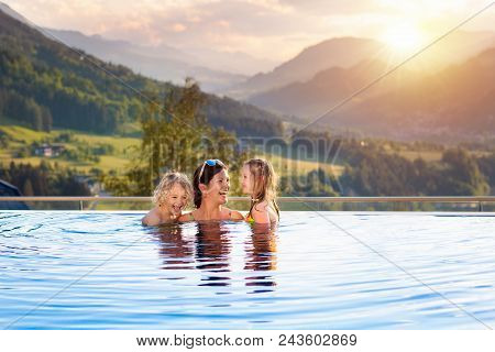 Kids Play In Outdoor Infinity Swimming Pool Of Luxury Spa Alpine Resort At Sunset In Alps Mountains.