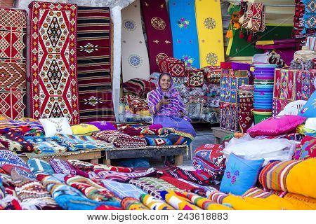 Doha, Qatar - December 25, 2017 : Female Trader At Souq Waqif Market In Doha, With Multicolour Carpe