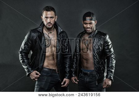Machos With Muscular Torsos Look Attractive In Leather Jackets, Dark Background. Men On Confident Fa