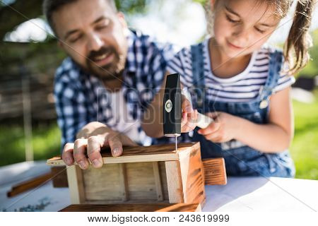 Father With A Small Daughter Outside With Hammer Making Wooden Birdhouse Or Bird Feeder.