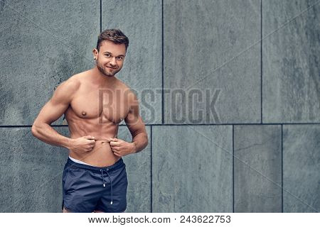 Fit Muscular Shirtless Young Man Pinching His Belly Skin In A Concept Of Belly Fat As He Stands Agai