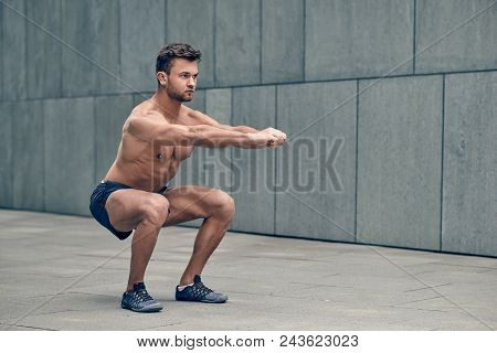 Fit Muscular Shirtless Young Man Working Out In Town Doing Squats In A Forecourt Of A Commercial Bui