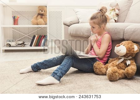 Sad Little Girl Watching Movie. Sorry Female Kid Sitting On Floor, Home Alone, Watching Cartoon On L