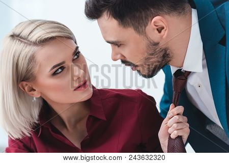Young Business People Looking At Each Other While Businesswoman Holding Necktie Of Handsome Business