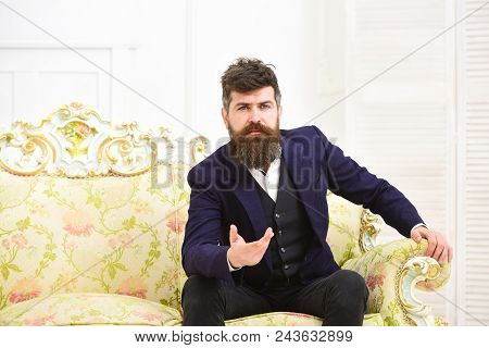 Man With Beard And Mustache Wearing Classic Suit, Sits On Old Fashioned Armchair Or Sofa. Speaker, W