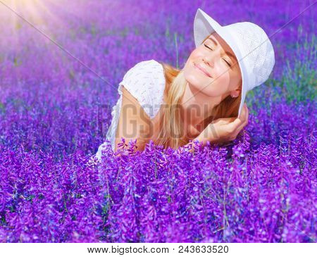 Pretty woman sitting on lavender field at sunny day, beautiful female on purple flowers meadow, cheerful smiling girl enjoying violet floral glade and sun light, portrait of young lady