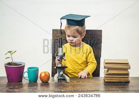 Kid Boy With Microscope. Smart Small Boy, Scientist Child In Academic Cap Works With Microscope. Ear