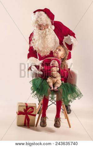 Christmas Portrait Of Cute Little Newborn Baby Girl, Pretty Teen Sister, Dressed In Christmas Clothe