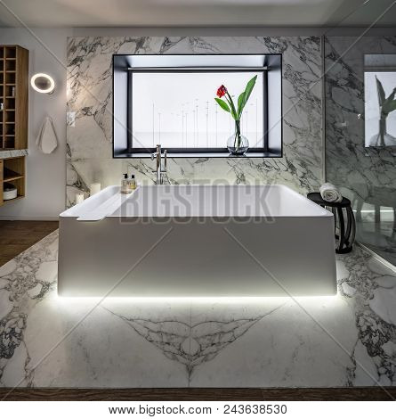 Nice Modern Bathroom With White And Tiled Walls. There Is A Large White Bath With A Backlight On A W