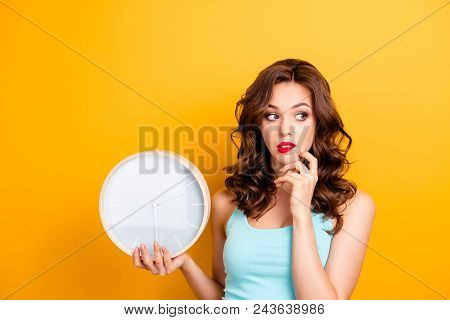 Portrait Of Thoughtful Confused Girl Holding Hand On Chin Looking To The Side Away Biting Lip Having