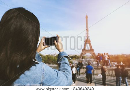 Woman Tourist Taking Photo By Phone Near The Eiffel Tower In Paris Under Sunlight And Blue Sky. Famo