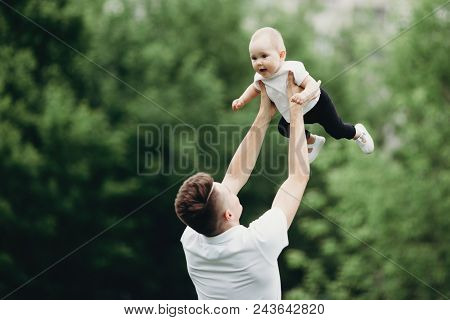 Happy joyful child playing with father outdoors. Daddy and daughter having fun, dad throwing up in the air his laughing baby. Father's day, loving family, childhood, parenting, fatherhood poster