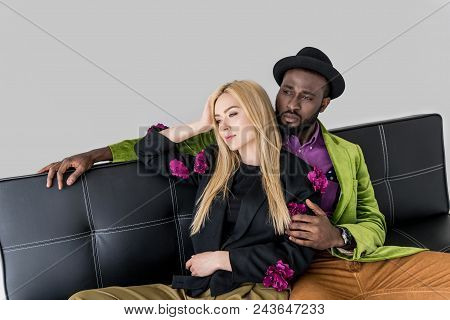 Pensive Multicultural Fashionable Couple On Black Sofa Isolated On Grey
