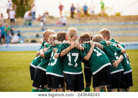 Young Football Soccer Players In Sportswear. Young Sports Team With Football Coach. Pep Talk With Co