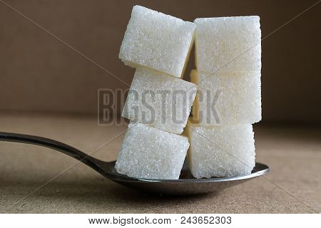 Six Pieces Of Sugar In A Metal Spoon On A Light Brown Background, A Surplus Of Sugar