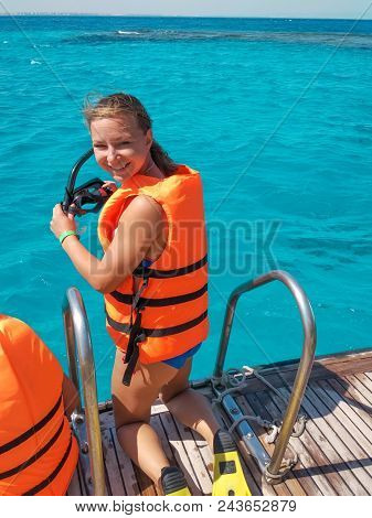 Portrait Of Smiling Woman Wearing Life Vest And Holding Diving Mask Going To Dive Into The Water On