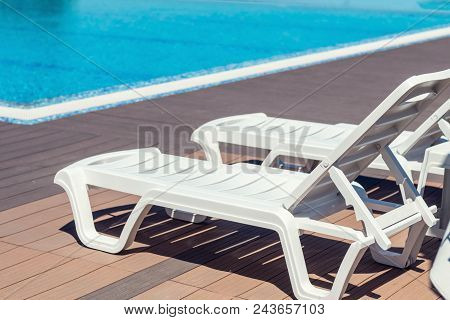 Swimming Pool With Wooden Deck At Hotel.summer Sunny Day. Lounge Chairs, Beach Sunbeds In A Swimming