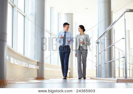 Vertrouwen zakenpartners in kantoor gebouw en praten lopen