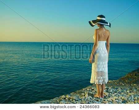 Elegant young woman in a hat standing on beach